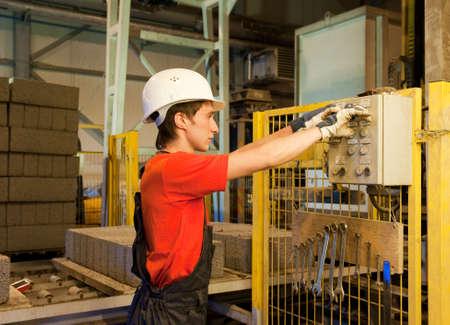 damaged cement: Factory worker fixing broken device