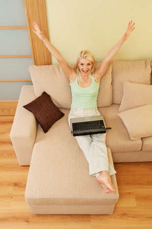 Happy young woman sitting on sofa with laptop     photo