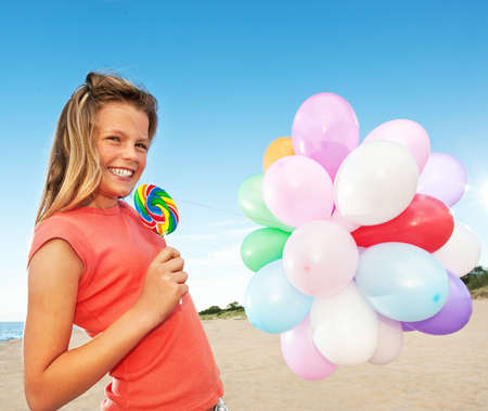 Happy girl with balloons and sweet candy photo