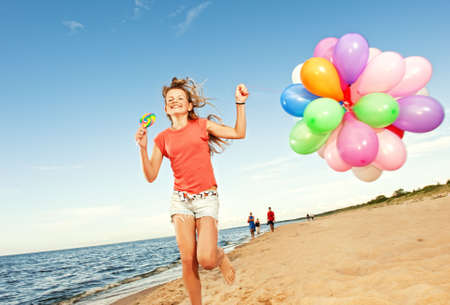 Happy girl with balloons running on the beach photo