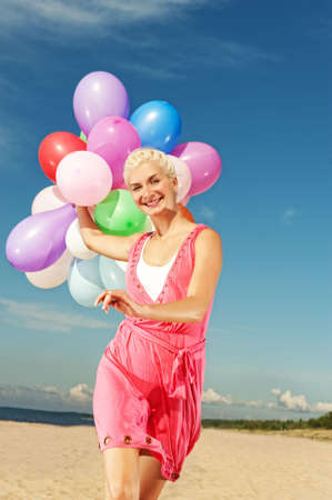 Happy girl with balloons running on the beach Stock Photo - 5258353