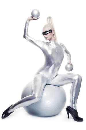 costume ball: Beautiful cyber woman sitting on a silver ball