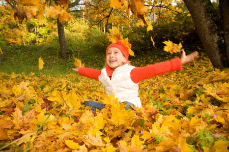 fall fun: Beautiful little girl with autumn leaves outdoors