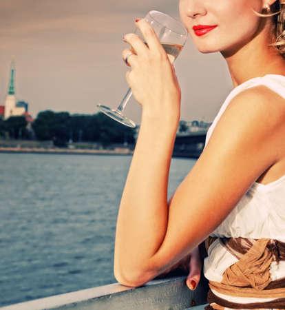 Beautiful woman drinks chamlagne near the river Stock Photo - 5334542