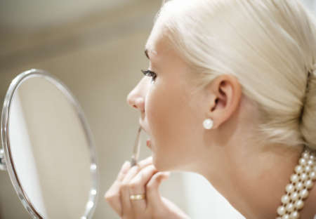 mujer maquillandose: Mujer de aplicar el maquillaje (Shallow DOF, se centran en los ojos)