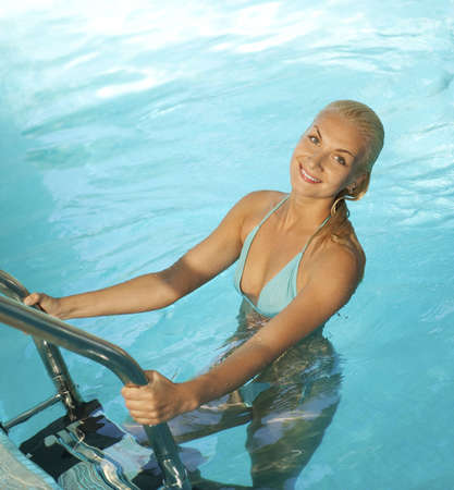 Beautiful blond woman relaxing in the pool      photo
