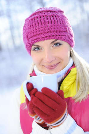 Beautiful blond woman drinking hot tea outdoors      photo