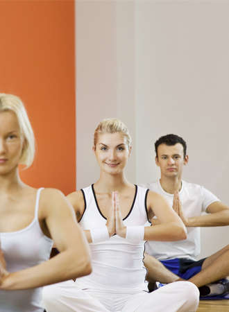 Group of people doing yoga exercise (focus on a woman in the middle)  photo