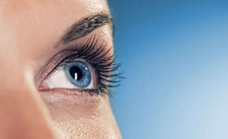 cosmetic surgery: Eye on blue background (shallow DoF)