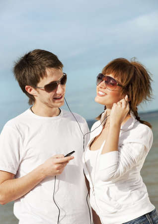 Happy young couple listening to music together photo