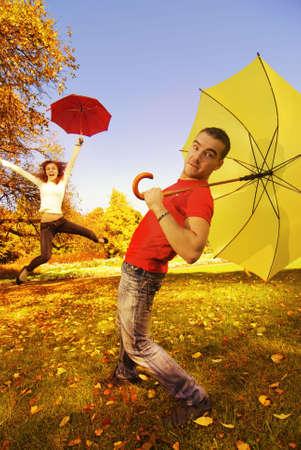 uomo sotto la pioggia: Funny coppia con ombrelloni in autunno background Archivio Fotografico