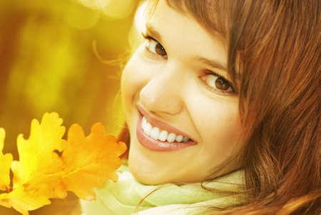 Beautiful romantic brunette with golden autumn leaf close-up portrait photo