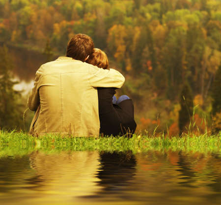 romantic hug: Sweet couple sitting on a hill and looking at the autumn landscape