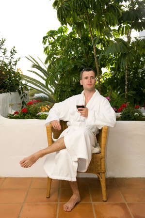 Young handsome men drinking wine after bath photo