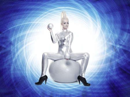 Beautiful cyber woman sitting on a silver ball      photo