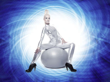 Beautiful cyber woman sitting on a silver ball      photo
