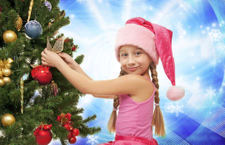 Little santa girl decorating the christmas tree  Stock Photo - 5618972