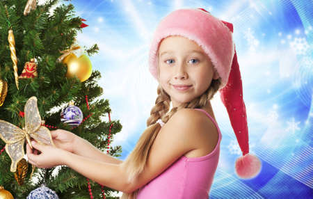 Little santa girl decorating the christmas tree   Stock Photo - 5618975