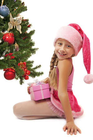 Happy Santa girl near the christmas tree      photo
