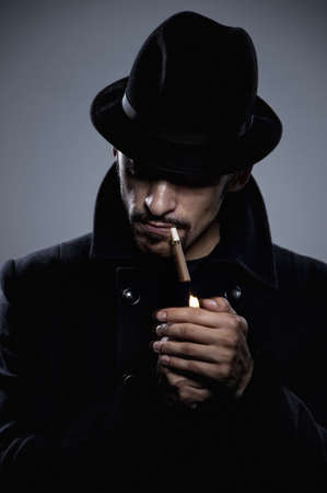 Mysterious man lighting a cigarette photo