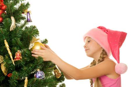 Little santa girl decorating the christmas tree photo