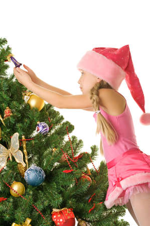 Little santa girl decorating the christmas tree photo