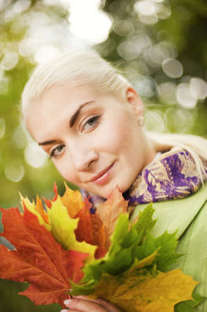 Beautiful romantic woman with golden autumn leaves close-up portrait photo