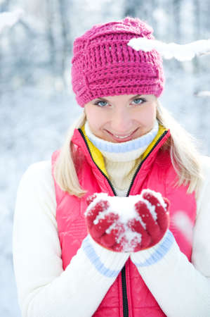 Smiling beautiful woman playing with snow      photo
