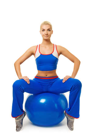 Young happy woman doing exercise on a fitness ball photo