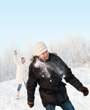 Funny couple playing snowballs photo