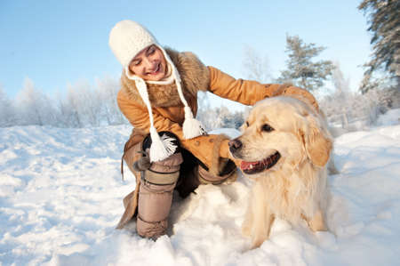 bosque con nieve: Mujer feliz jugando con golden retriever al aire libre