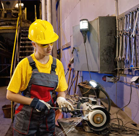 Factory female worker sharpening tools Stock Photo - 6327351