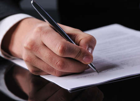 policies: businessman writing on a form