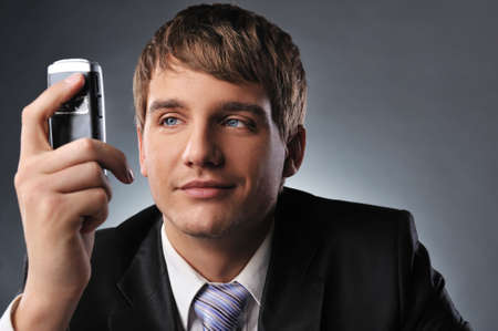 Young businessman holding mobile phone photo
