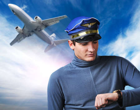 Handsome pilot against blue sky and flying plane photo