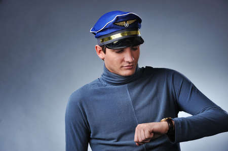 Handsome pilot looking to his watch. Isolated on grey background Stock Photo - 6423314