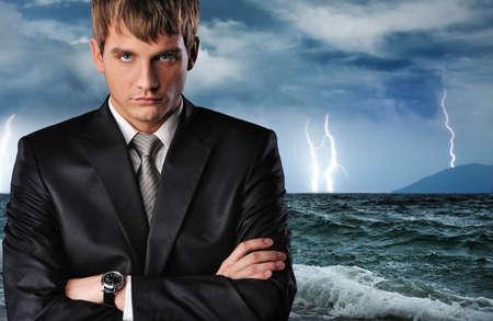 modern businessman: Seriour businessman over dark stormy sky