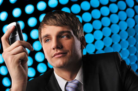 Young businessman holding mobile phone over abstract background  photo