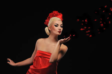 Beautiful woman blowing rose petals photo