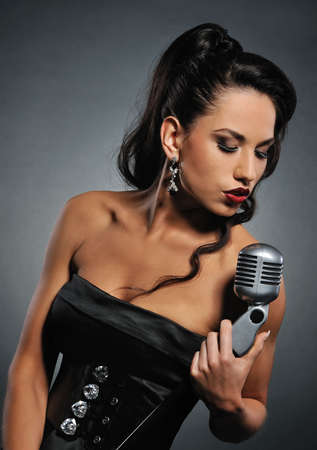 silver dress:  Beautiful brunette woman singing   Stock Photo