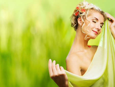 wellness environment: Beautiful young woman with fresh flowers in her hair. Spring concept.  Stock Photo