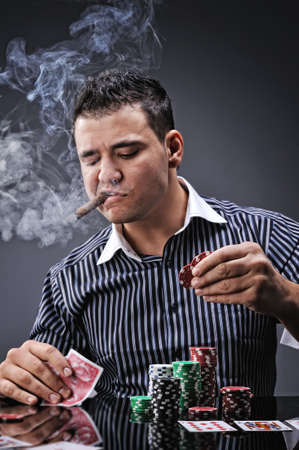Portrait of a young gangster smoking and playing poker photo