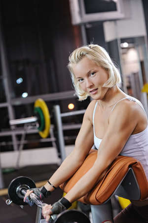 Strong beautiful woman lifting heavy weights  photo