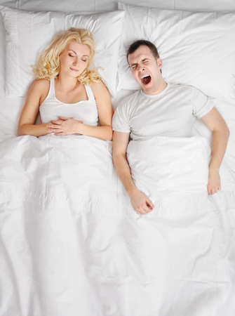 yawning: Young couple sleeping in a bed
