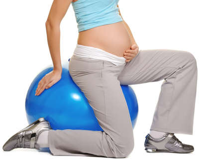 Young pregnant woman making exercise on a fitness ball  photo