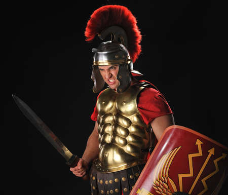 cascos romanos: Soldado de legionario enojado con un gladius y escudos Foto de archivo