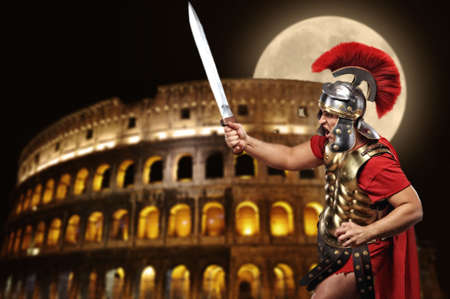 Roman legionary soldier in front of coliseum at night time photo