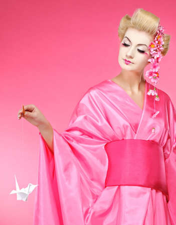Beautiful geisha with an origami bird Stock Photo - 6745269