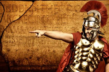 casco rojo: Soldado legionario en frente de la muralla romana Foto de archivo