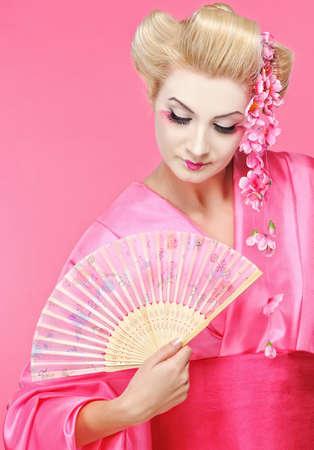 Portrait of a beautiful geisha with fan  photo
